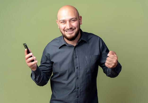 Uomo calvo giovane gioioso della call center che tiene il telefono cellulare e il pugno di serraggio isolato su verde oliva
