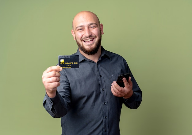 Joyful young bald call center man holding mobile phone and stretching out credit card isolated on olive green