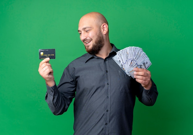 Joyful young bald call center man holding money and credit card looking at card isolated on green