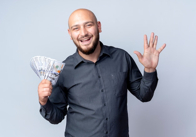 Gioioso giovane uomo calvo call center che tiene i soldi e che mostra cinque con la mano isolata su bianco