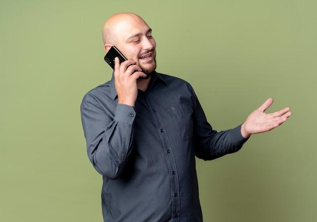 Uomo calvo giovane gioioso della call center che guarda al lato che parla sul telefono e che mostra la mano vuota isolata su verde oliva