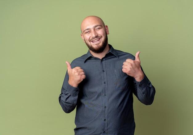 Gioioso giovane uomo calvo della call center che mostra i pollici in su isolato su verde oliva