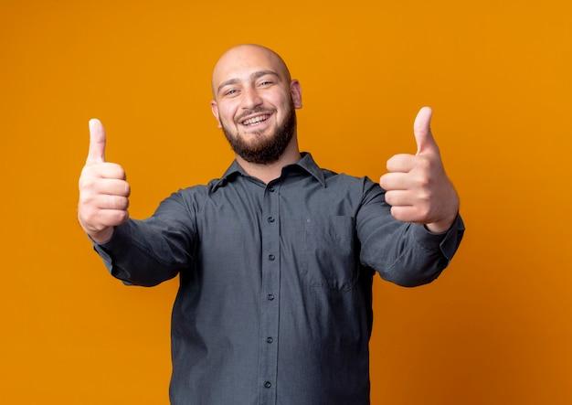 Joyful young bald call center man showing thumbs up isolated on orange