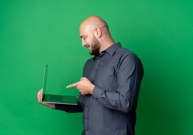 Joyful young bald call center man standing in profile view holding and pointing at laptop isolated on green