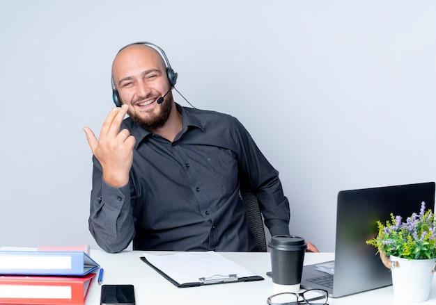白で隔離の手でピストルサインを行う作業ツールと机に座っているヘッドセットを身に着けているうれしそうな若いハゲのコールセンターの男