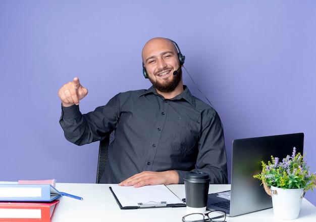 紫色で隔離された作業ツールを指している机に座っているヘッドセットを身に着けているうれしそうな若いハゲのコールセンターの男