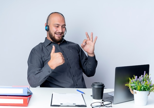 Joyful young bald call center man wearing headset sitting at desk with work tools doing ok sign and showing thumb up at laptop isolated on white