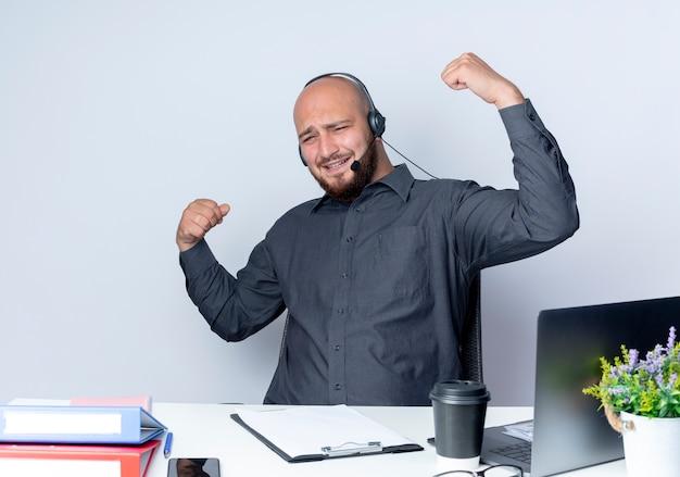 Joyful giovane call center calvo uomo che indossa la cuffia avricolare seduto alla scrivania con strumenti di lavoro gesticolando forte isolato su bianco