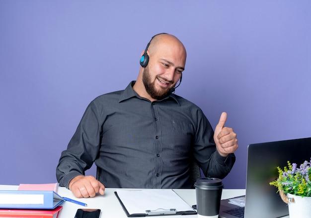 Joyful giovane call center calvo uomo che indossa la cuffia avricolare seduto alla scrivania con strumenti di lavoro guardando il computer portatile e mostrando il pollice in alto isolato su viola