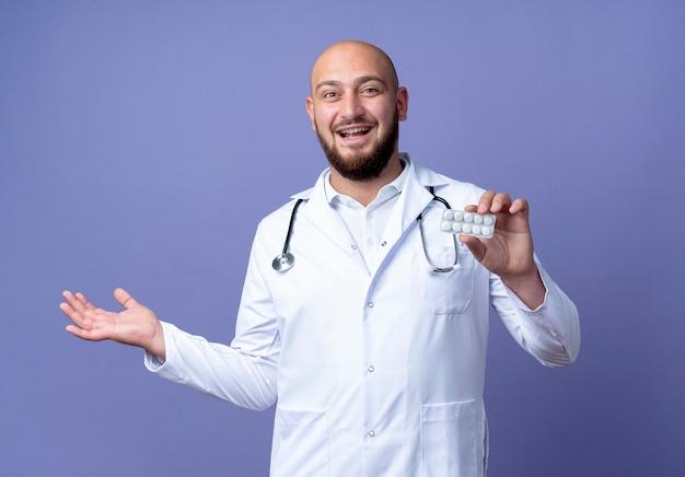 Gioioso giovane medico maschio calvo indossando abito medico e stetoscopio tenendo pillole e punti con mano a lato isolato su sfondo blu