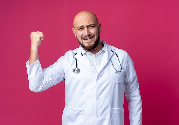 Joyful young bald male doctor wearing medical robe and stethoscope showing strong gesture isolated on pink wall