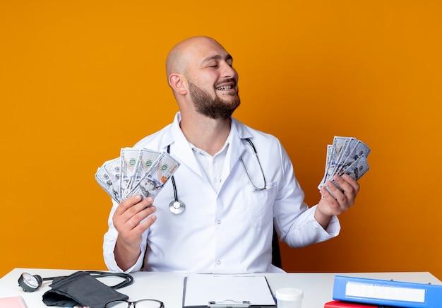Gioioso giovane medico maschio calvo che indossa una tunica medica e uno stetoscopio seduto alla scrivania del lavoro
