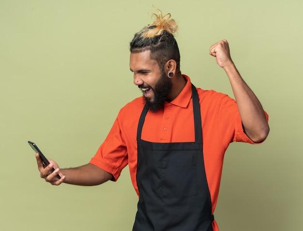 Радостный молодой парикмахер в униформе, держащийся и смотрящий на мобильный телефон, делает жест да, изолированный на оливково-зеленой стене
