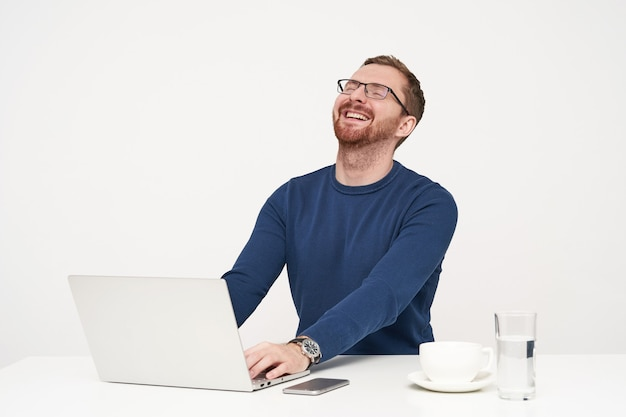 笑いながら目を閉じたまま頭を投げ返し、白い背景の上で彼のラップトップで作業しながら面白い冗談を聞いてうれしそうな若いひげを生やした金髪の男