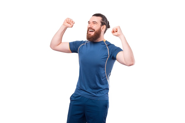 Joyful young bearded fitness man celebrating success on white
