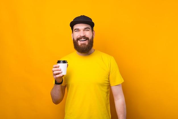 이동 중에 커피 한잔 마시는 즐거운 젊은 수염 된 hipster 남자