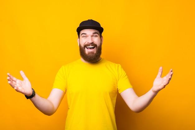 黄色で歓迎のジェスチャーをしているうれしそうな若いひげを生やした男、はじめまして