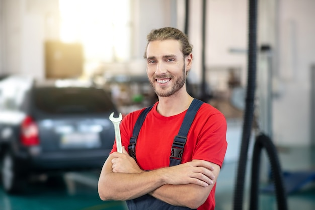 Joyful young bearded man motor mechanic in overalls with tool standing in workshop
