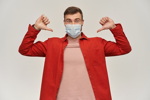 Gioioso giovane uomo barbuto in camicia rossa e maschera protettiva contro il virus sul viso contro il coronavirus che indica se stesso con entrambi i pollici sul muro bianco