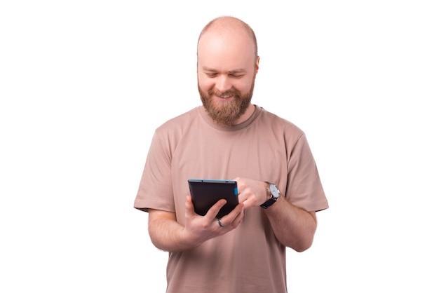 Радостный молодой бородатый мужчина с помощью планшета на белом