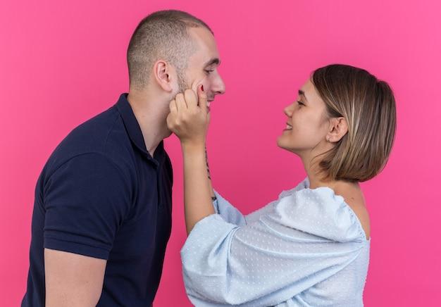 분홍색 벽 위에 서있는 그녀의 사랑스러운 남자 친구의 뺨을 꼬 집는 즐거운 젊은 아름다운 부부 웃는 여자