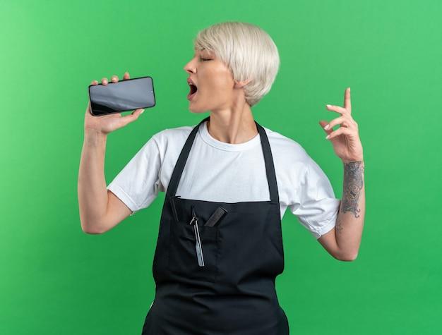 Радостная молодая красивая женщина-парикмахер в униформе держит телефон и поет на зеленой стене