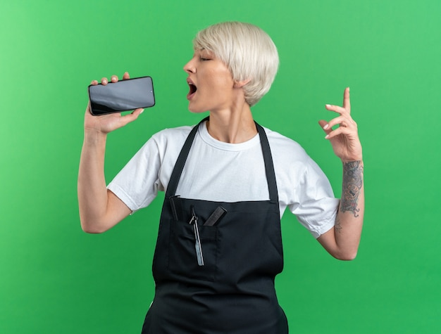 Joyful young beautiful female barber in uniform holding phone and singing isolated on green wall