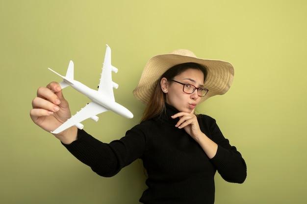 Gioiosa giovane bella ragazza in un dolcevita nero e bicchieri che tengono aeroplano giocattolo con espressione scettica