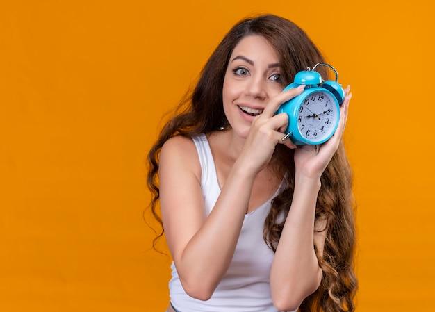 Радостная молодая красивая девушка держит будильник на изолированном оранжевом пространстве с копией пространства
