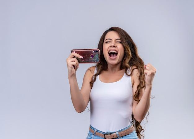 Радостная молодая красивая девушка держит мобильный телефон и поднимает кулак с закрытыми глазами с копией пространства