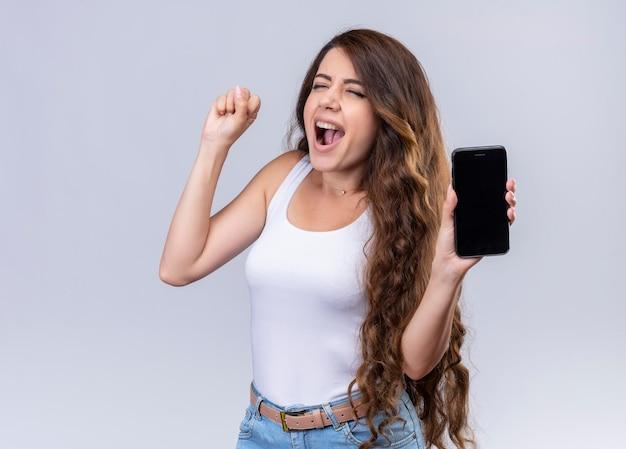 Радостная молодая красивая девушка держит мобильный телефон и поднимает кулак с копией пространства