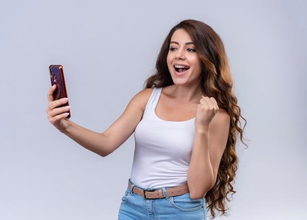 Радостная молодая красивая девушка держит мобильный телефон, глядя на него с поднятой рукой