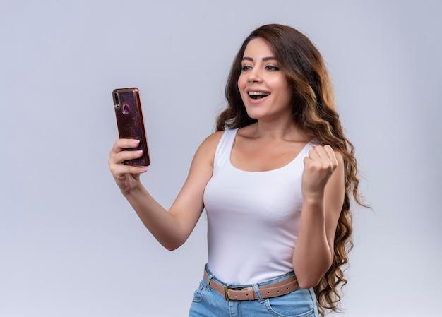 Gioiosa giovane bella ragazza che tiene il telefono cellulare guardandolo e alzando il pugno