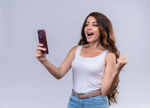 Gioiosa giovane bella ragazza che tiene il telefono cellulare e guardandolo con il pugno alzato