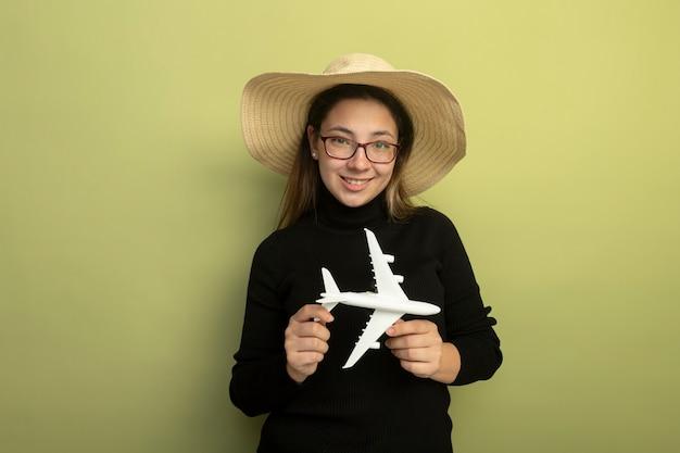 검은 터틀넥과 장난감 비행기를 들고 안경에 즐거운 젊은 아름다운 소녀가 행복하고 긍정적으로 웃고 있습니다.