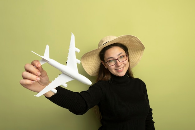 검은 터틀넥과 장난감 비행기를 들고 안경에 즐거운 젊은 아름다운 소녀 유쾌하고 행복하고 긍정적 인 미소