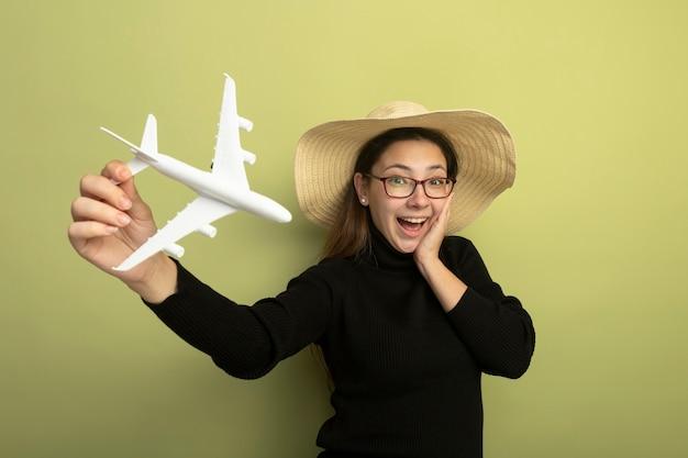 검은 터틀넥과 장난감 비행기를 들고 안경에 즐거운 젊은 아름다운 소녀 놀라게하고 행복한 얼굴로 놀랐습니다.