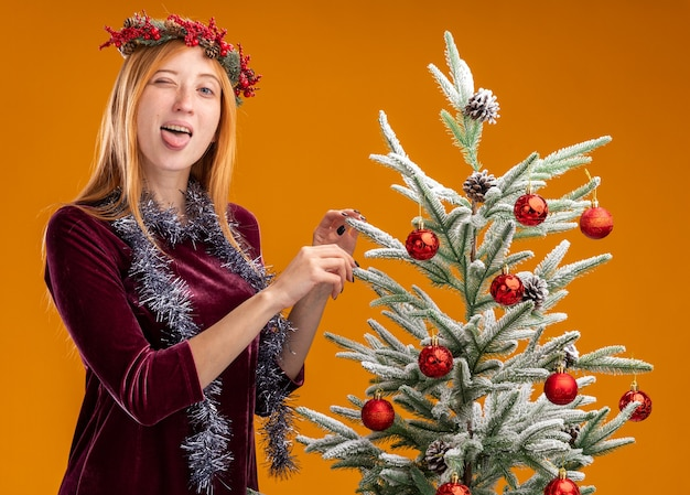 Joyful young beautiful girl standing nearby christmas tree wearing red dress and wreath with garland on neck showing tongue isolated on orange background
