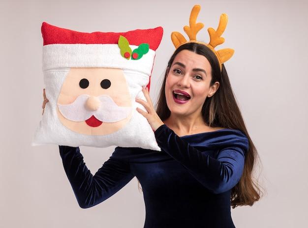 青いドレスと白い背景で隔離の顔の周りにクリスマス枕を保持してクリスマスの髪のフープを身に着けているうれしそうな若い美しい少女