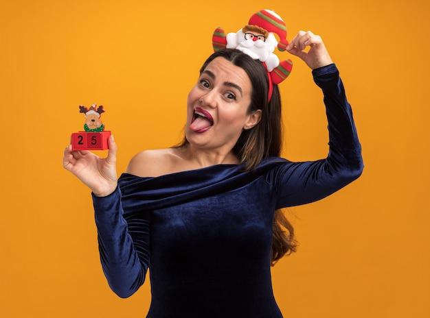 오렌지 배경에 고립 된 혀를 보여주는 장난감을 들고 파란 드레스와 크리스마스 머리 후프를 입고 즐거운 젊은 아름 다운 소녀