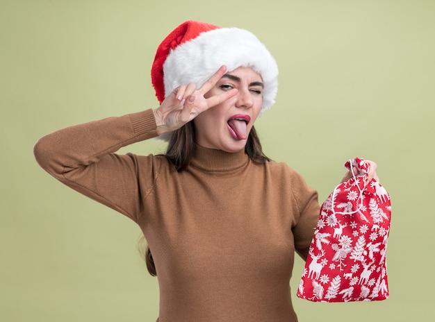 オリーブグリーンの壁に分離された舌と平和のジェスチャーを示すクリスマスバッグを保持しているクリスマスの帽子をかぶってうれしそうな若い美しい少女