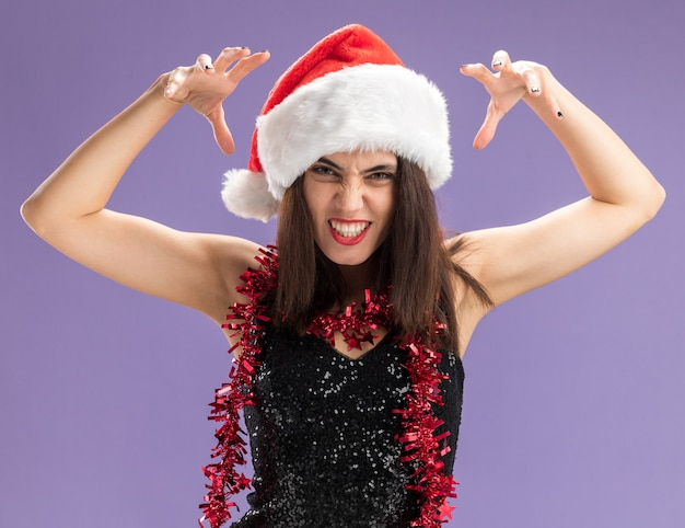 Joyful young beautiful girl wearing christmas hat with garland on neck showing tiger style gesture isolated on purple background