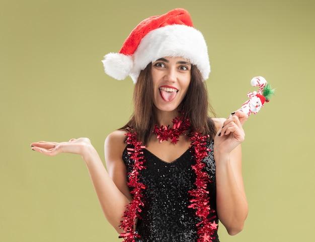オリーブグリーンの背景に分離された舌を示すクリスマスのおもちゃを広げて手を持って首に花輪とクリスマスの帽子をかぶってうれしそうな若い美しい少女