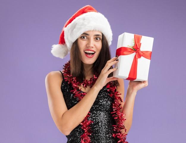 보라색 배경에 고립 된 선물 상자를 들고 목에 갈 랜드와 함께 크리스마스 모자를 쓰고 즐거운 젊은 아름 다운 소녀