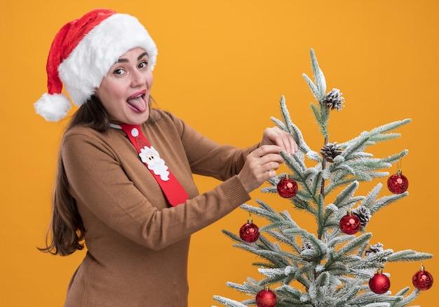 오렌지 배경에 고립 된 크리스마스 트리 근처 서 넥타이와 크리스마스 모자를 쓰고 즐거운 젊은 아름 다운 소녀