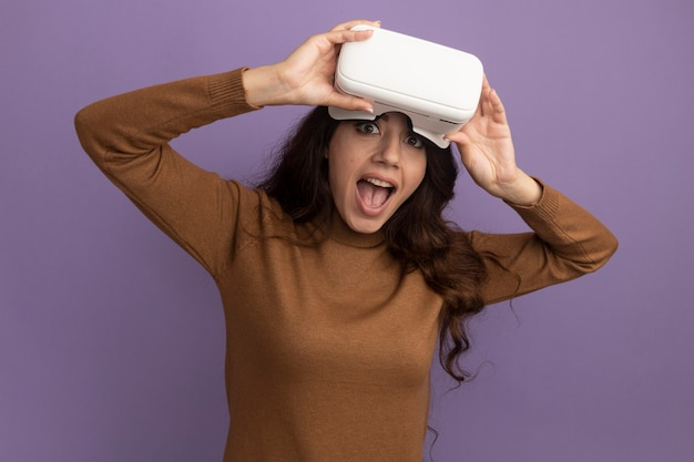 Joyful young beautiful girl wearing and holding vr headset isolated on purple wall