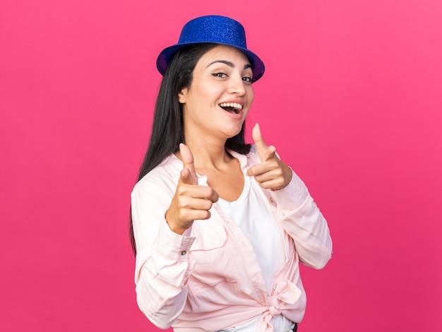 카메라에 파티 모자 포인트를 입고 즐거운 젊은 아름 다운 소녀