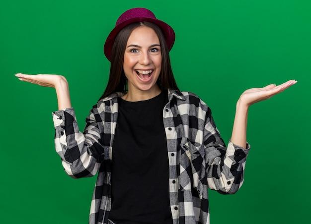 緑の壁に分離された手を広げてパーティハットを身に着けているうれしそうな若い美しい少女