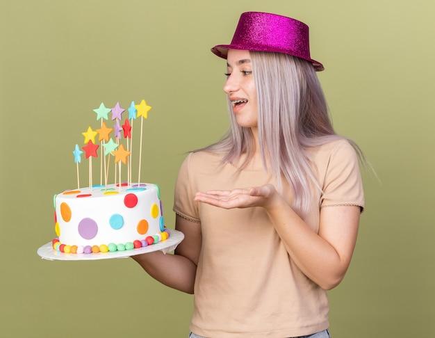 치과 교정기를 들고 파티 모자를 쓰고 올리브 녹색 벽에 격리된 손 케이크를 가리키는 즐거운 젊은 아름다운 소녀
