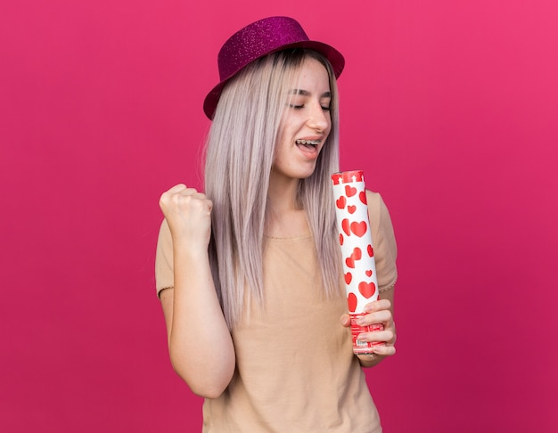 Joyful young beautiful girl wearing party hat with dental braces holding confetti cannon and singing isolated on pink wall